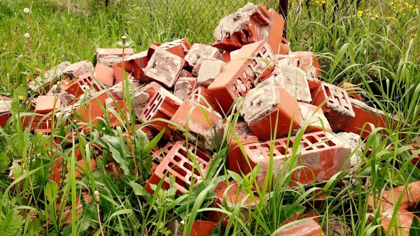 A pile of old red bricks on the grass | Shutterstock HD Video #1053402872