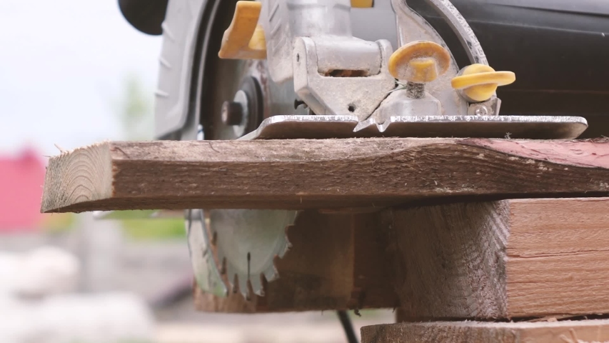 A man saws a tree with a circular saw. | Shutterstock HD Video #1053402881