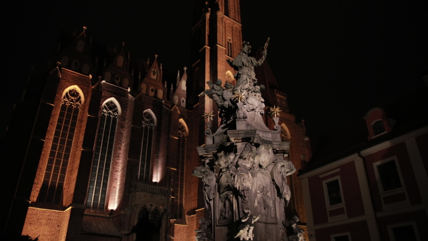 Night Cathedral Of St. John The Baptist In Wroclaw In Foreground Is A Statue Jesus Christ With Angels | Shutterstock HD Video #1053403088