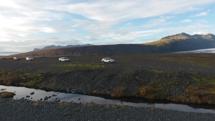 Four jeeps ride on a gravel road amid mountains and a glacier. Travel through the mountains and glaciers of Iceland | Shutterstock HD Video #1053404780