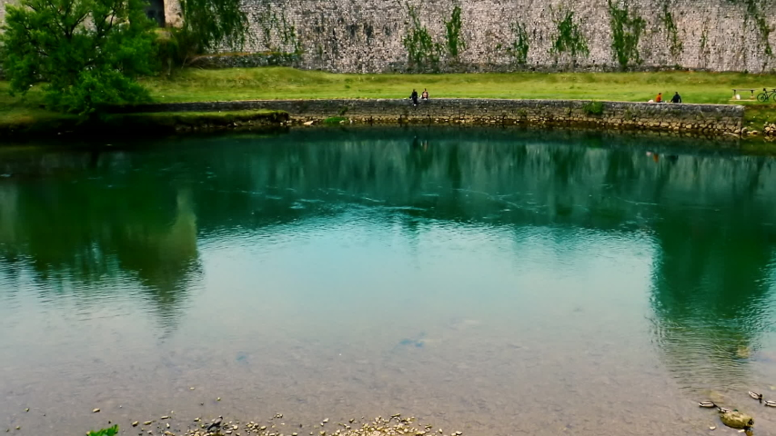 A few people are sitting at river bank in front of remains of old Roman fortress while calm green river is passing by. | Shutterstock HD Video #1053404834