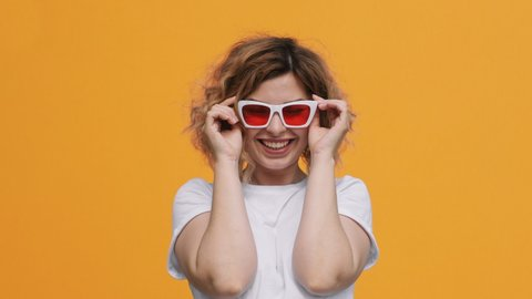 Portrait of happy pretty woman stylish white sunglasses with red glasses raises  up, smiling with pleasure on yellow background slow motion in summer. Emotions. Positive girl. Lifestyle