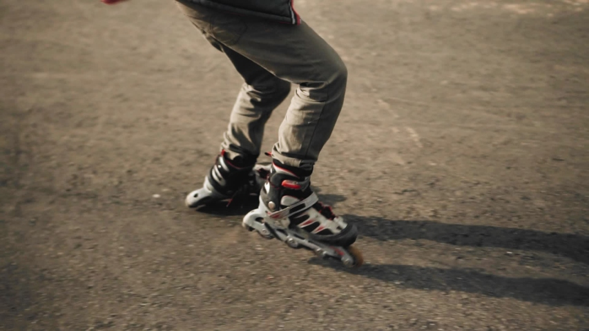 A boy rides on roller skates on the asphalt. The guy's shadow falls to the ground | Shutterstock HD Video #1053407747