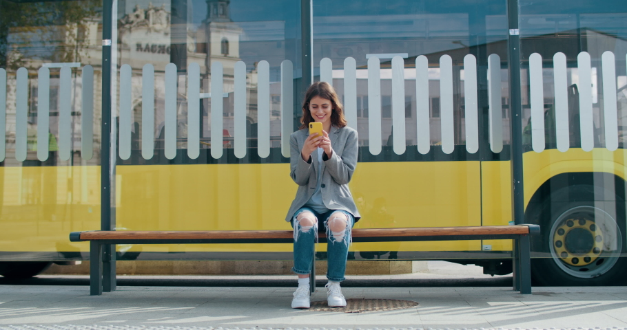 Cheerful woman wearing casual clothes browsing internet or chatting in social networks. Pretty girl using smartphone while sitting at public transport stop. Bus riding at background | Shutterstock HD Video #1053408380
