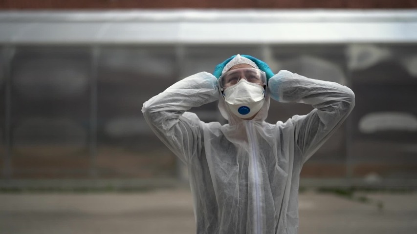 Exhausted crying doctor/nurse in coronavirus protective gear N95 mask.Covid-19 pandemic outbreak.Fatalities grief.Frontline worker mental stress,burnout.Mental breakdown.Overworked healthcare provider Royalty-Free Stock Footage #1053409040