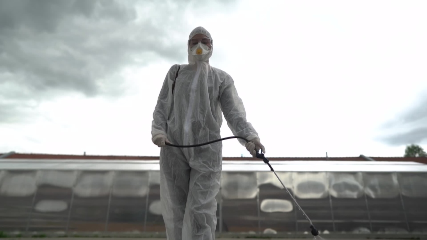 Sanitation worker in hazmat protection suit and N95 mask with chemical decontamination sprayer tank.Disinfecting streets and public areas to stop COVID-19 spread.Coronavirus disinfection concept Royalty-Free Stock Footage #1053409085