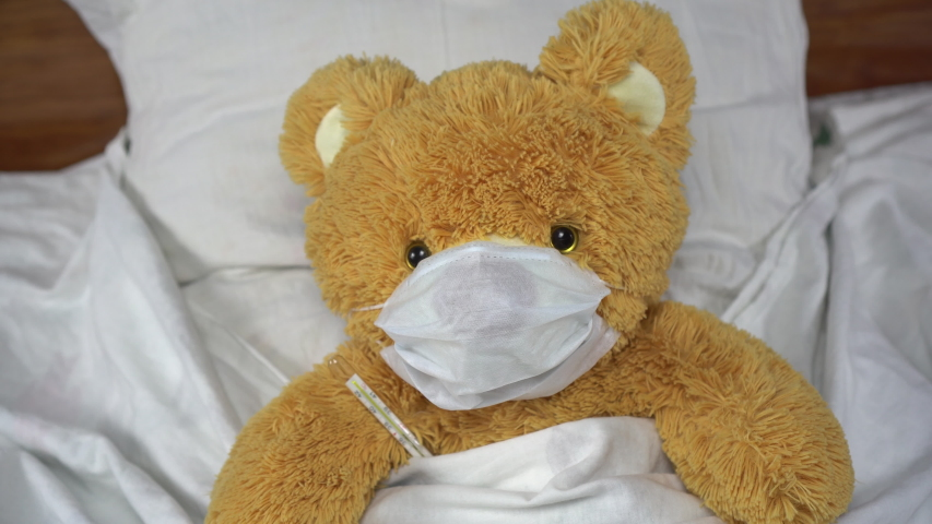 A teddy bear measures the temperature with a mercury thermometer. The bear lies in bed with a medical mask.