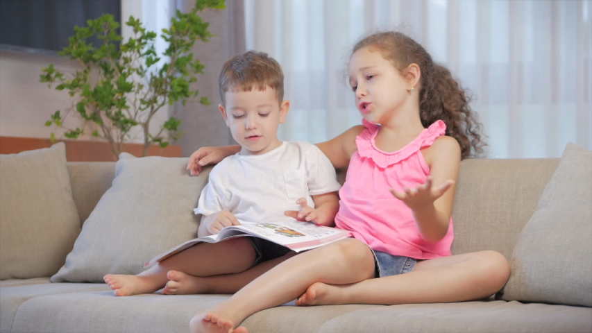 Cute children,sister with a younger brother, looking at a book magazine textbook dictionary tablet read fairy tales, kids are reading books sitting on the couch,preschool and school education. Royalty-Free Stock Footage #1053413039