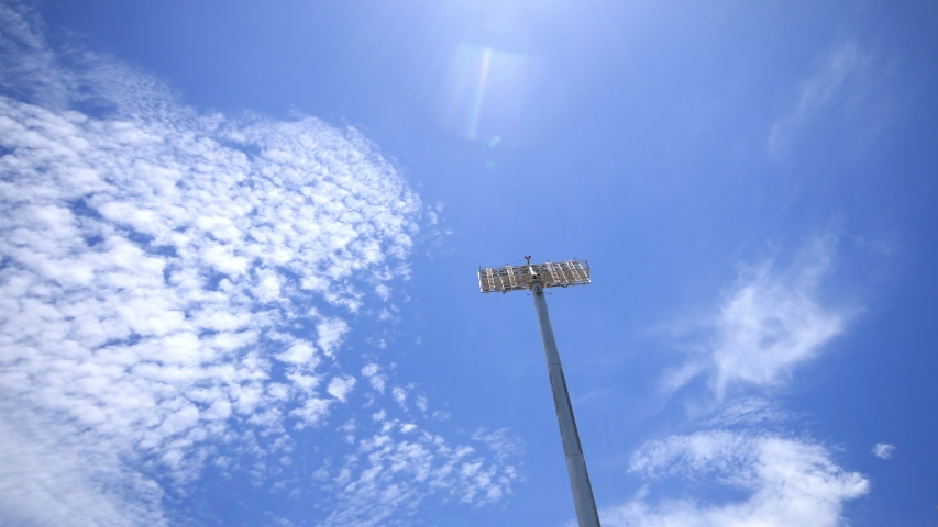 Stadium Lights In A Blue Sky Background. Stadium lights pole seen from the bottom. Timelapse of the clouds moving in a bright blue sky. | Shutterstock HD Video #1053413843