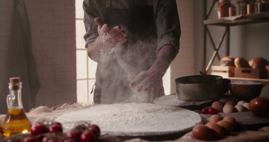 Experienced mature chef applying flour on hands before making traditional bread at bakery. Old man baking at home, enjoying hobby - closeup shot 4k footage