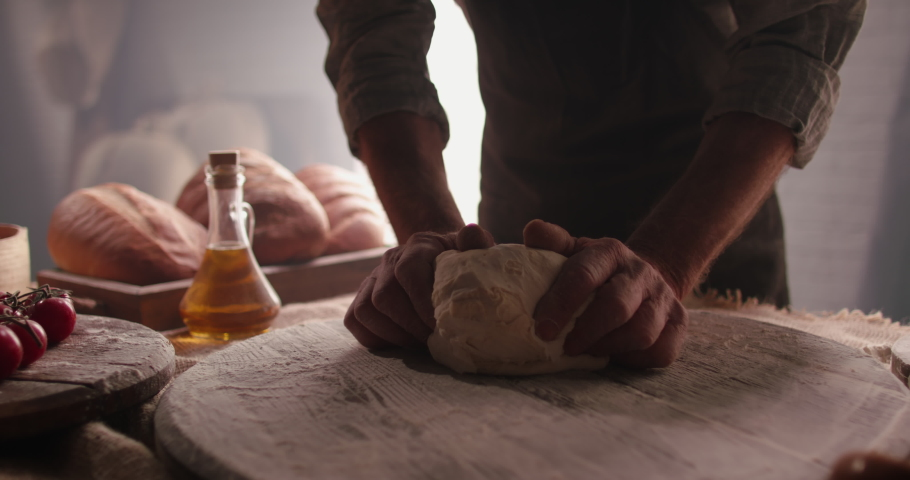 Hands of senior professional chef kneading floured dough for bread in bakery shop in the morning. Retiree enjoying new hobby making homemade bread close up 4k footage
