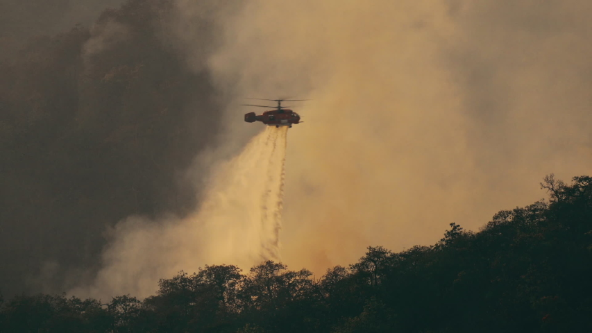 KA-32 Fire fighting helicopter dropping water on forest fire