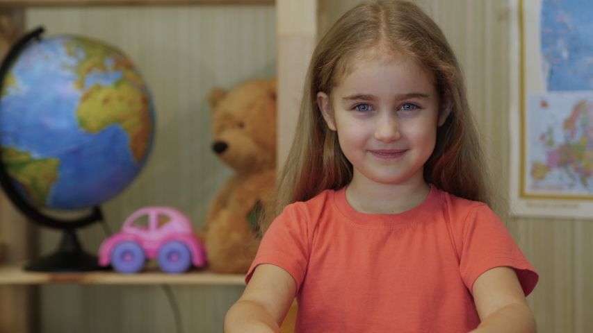 Kid Child Girl Making Online Video Call Recording Vlog Sitting by Table , Portrait. Funny Girl Smiling Looking At Camera. Happy Cute Little Vlogger Saying Hello Hi Looking At Camera Talking To Webcam Royalty-Free Stock Footage #1053419822