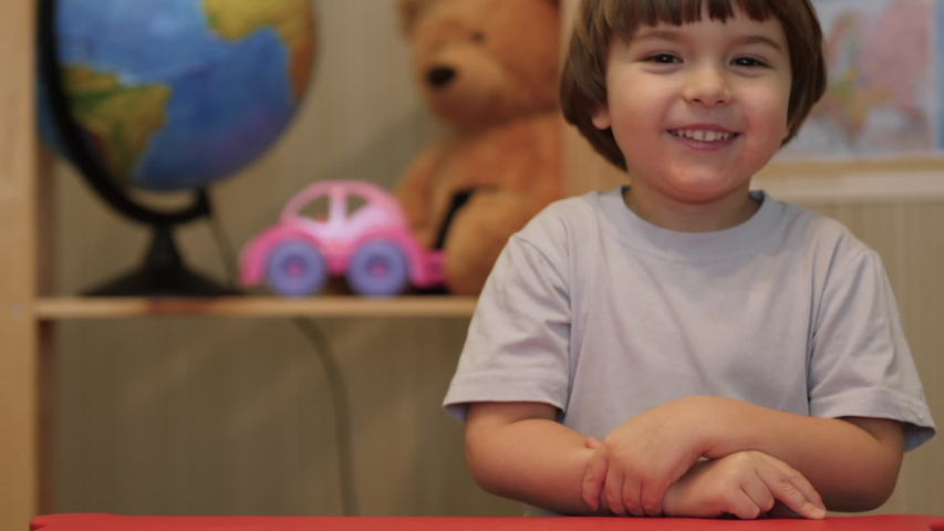 Kid Child Boy Making Online Video Call Recording Vlog Sitting by Table , Portrait. Funny Boy Smiling Looking At Camera. Happy Cute Little Vlogger Saying Hello Hi Looking At Camera Talking To Webcam. Royalty-Free Stock Footage #1053419831