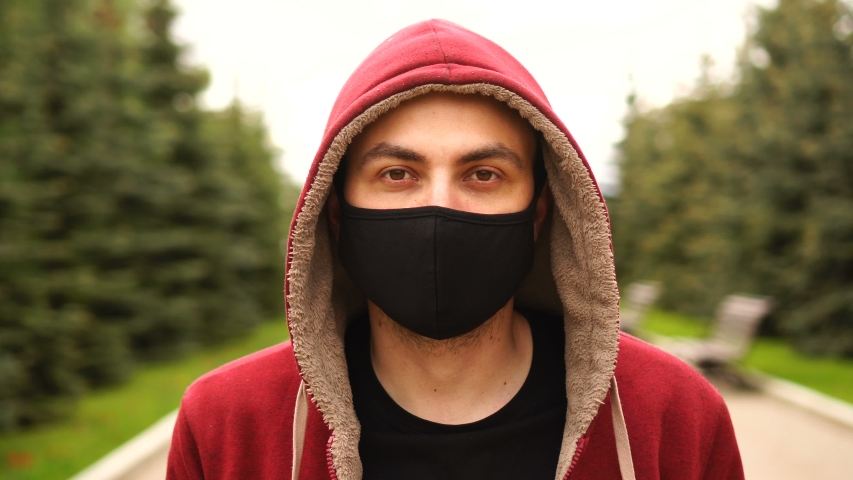 Portrait of a young man in hood, who wearing a protective medical mask on the street. Health and safety concept, N1H1 coronavirus, virus protection, pandemic, quarantine. | Shutterstock HD Video #1053423893