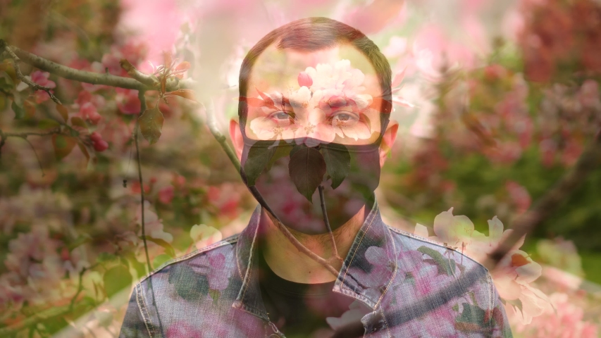 Overlay effect of man wearing black medical mask on blossom pink tree. | Shutterstock HD Video #1053423896