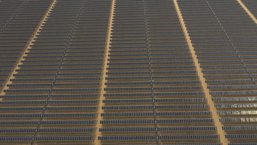Aerial view of photovoltaic panels in a desert solar farm | Shutterstock HD Video #1053424877