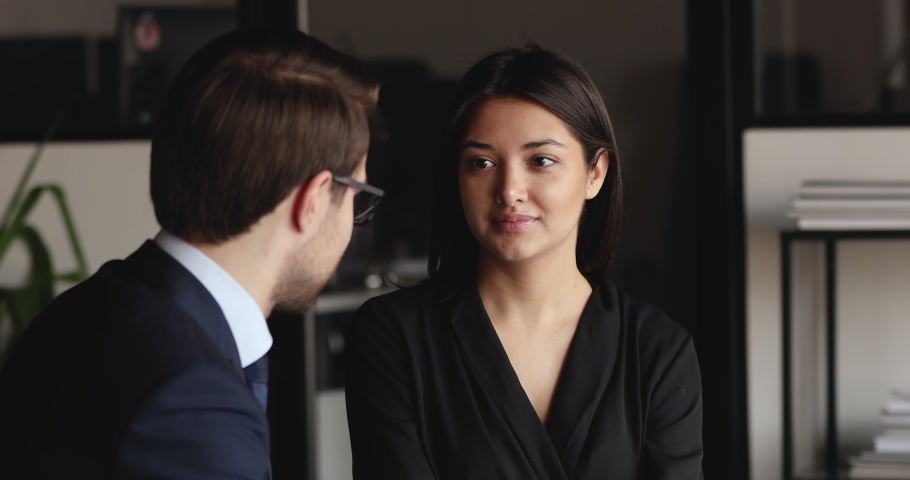 Diverse partners colleagues having business conversation in office. Male caucasian manager consulting female indian client at meeting. Young ethnic lady candidate talking to employer at job interview. Royalty-Free Stock Footage #1053424940