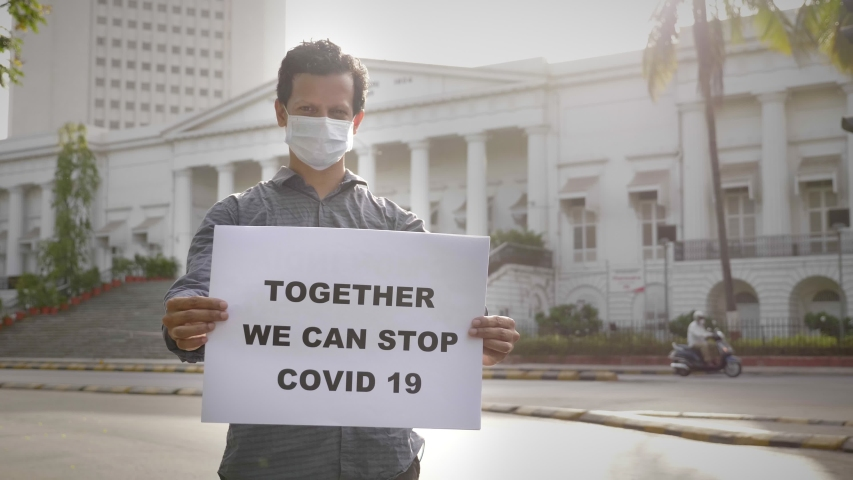 A young man wearing face mask standing and holding a placard with message 'Together we can stop COVID 19' next to Asiatic library on empty road during city lockdown amid coronavirus epidemic Royalty-Free Stock Footage #1053426413