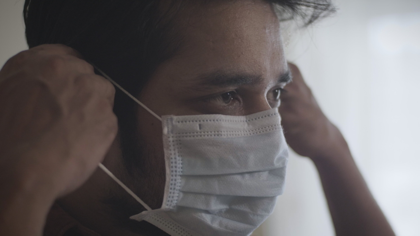A close up shot of a young man or male wearing or putting protective face mask amid Corona virus or COVID 19 epidemic or pandemic | Shutterstock HD Video #1053426416