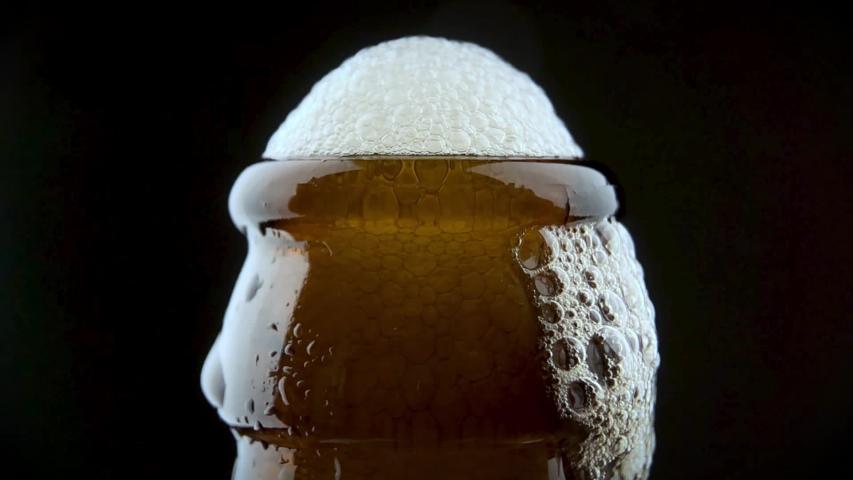 Men's hands open bottle of beer. Beer foam escapes from under the lid. | Shutterstock HD Video #1053426491