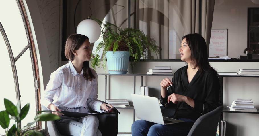 Young caucasian female hr manager talking with indian job applicant or colleague sitting in chairs in modern office. Two diverse businesswomen having business conversation during interview meeting. Royalty-Free Stock Footage #1053428612