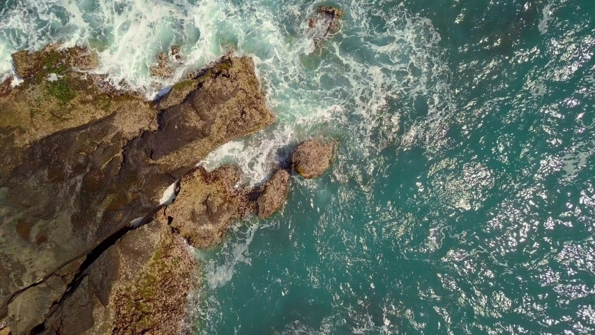 Zoom out aerial shot of big waves crashing into a huge stony cliff in blue ocean. Waves are splashing and breaking on the rocks with white seafoams. | Shutterstock HD Video #1053429119