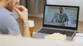Back view of happy man on video call with his friend drinking beer during coronavirus isolation.