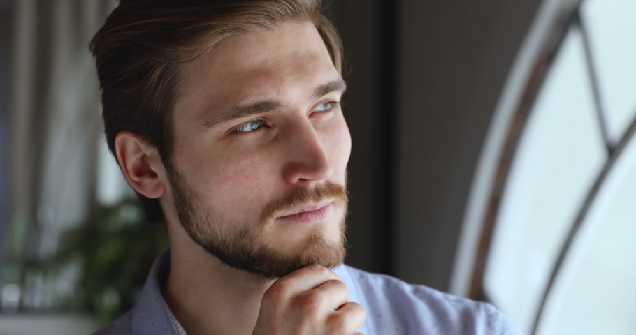 Worried thoughtful young businessman looking away thinking of future business challenges due financial crisis. Doubtful serious entrepreneur lost in thoughts considering risks, opportunities. Close up Royalty-Free Stock Footage #1053432986