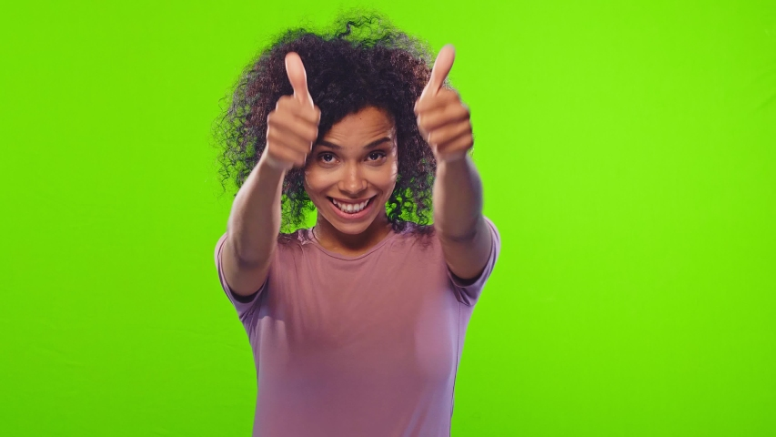 Charming cheerful beautiful african american positive woman showing thumbs up, gazes happy at camera and enjoying posing on green screen background. Positive feedback, body language concept