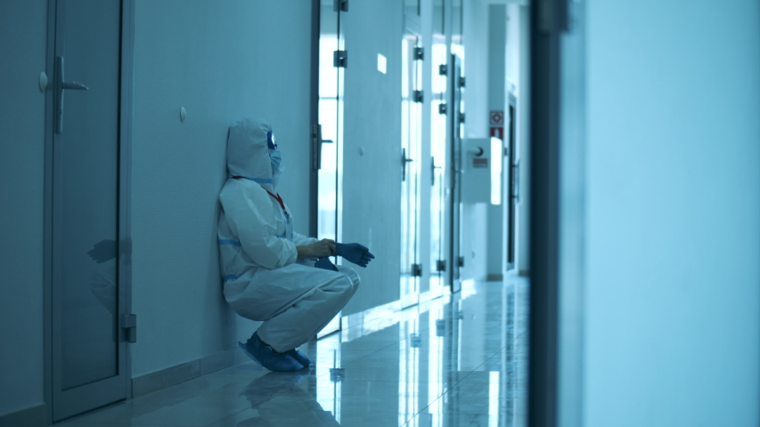 Female paramedic walks along the hall and sits down on the floor Royalty-Free Stock Footage #1053434096