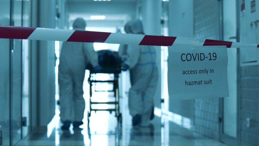 Covid-19 concept. Hazardous hall with doctors transporting a patient through it Royalty-Free Stock Footage #1053434105
