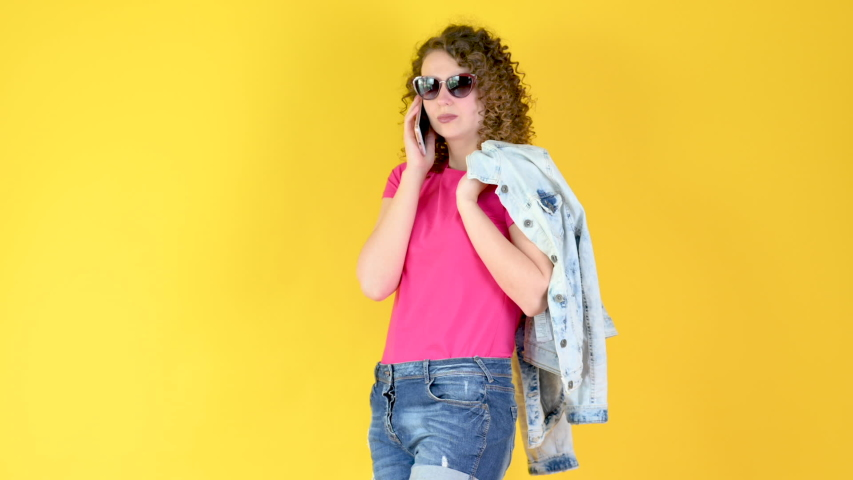 Happy young girl in sunglasses communicates on a smartphone isolated on a yellow background. using mobile phone have fun. People lifestyle concept. | Shutterstock HD Video #1053436274