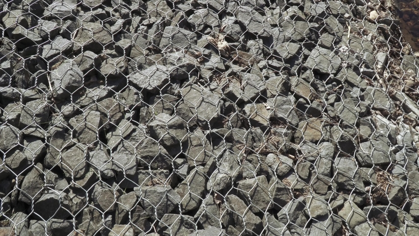 Stones reinforced with mesh netting on the banks of a stream in a city park | Shutterstock HD Video #1053437813