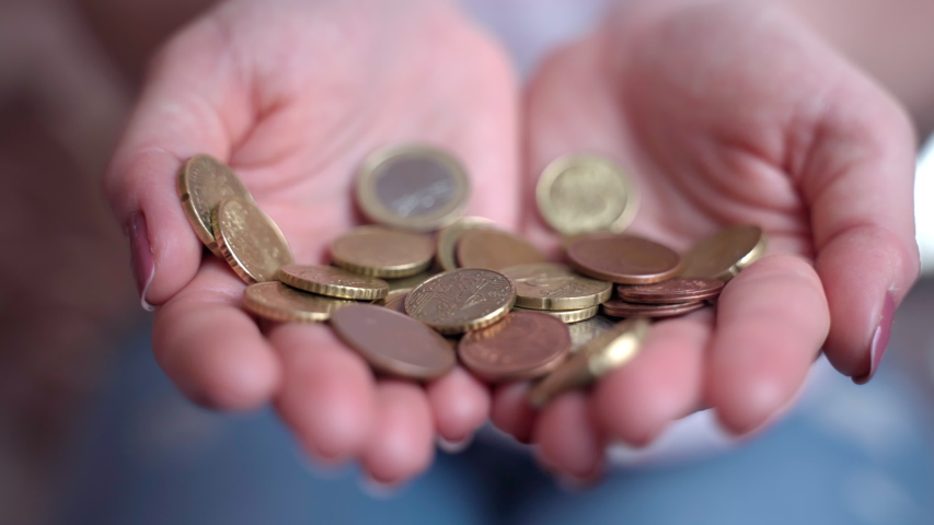 Close-up of falling coins in person's hands, making money and great savings for further financial investments in future. High income and profit, low expenses. Dealing with financial business sphere | Shutterstock HD Video #1053438746