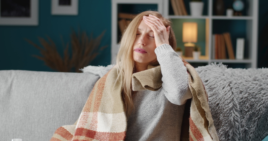 Unhappy woman with blond hair sitting on couch in warm blanket and suffering from headache. Mature female with blond hair coughing and sneezing while staying at home.