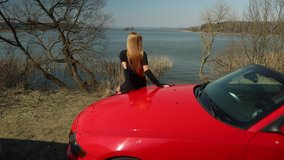 Video 4k clip, a young blonde woman with long hair sits on a red anchor car, looks at the lake on a sunny day in spring