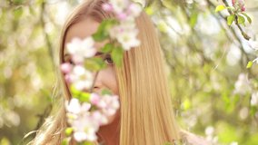 Video clip, blur effect and light fler, a young blonde woman with long hair in a long dress walks in a blossoming apple orchard on a sunny day in spring.