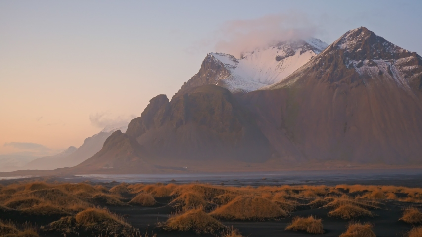 Vestrahorn mountain with black volcanic lava sand dunes at sunset, Stokksnes, Iceland   Shutterstock HD Video #1053443813