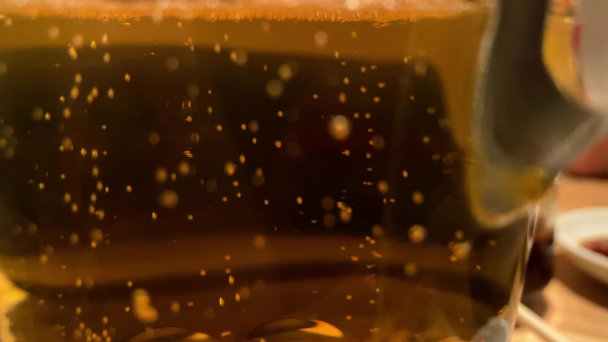 4K, Close up of fresh cold beer. Water drops on the glass surface, transparent yellow background. Lots of golden beer bubbles. Mug of beer on a wooden table in a pub.-Dan | Shutterstock HD Video #1053447881