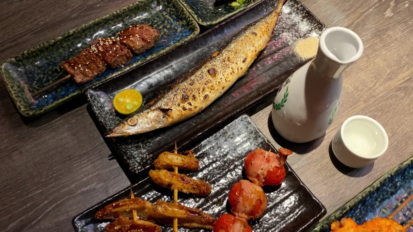 4K, Set of delicious traditional skewers grilled and a fish for dinner. Popular Japanese variety food in the restaurant. Appetizing Japan skewer plate on wooden table. -Dan | Shutterstock HD Video #1053447887