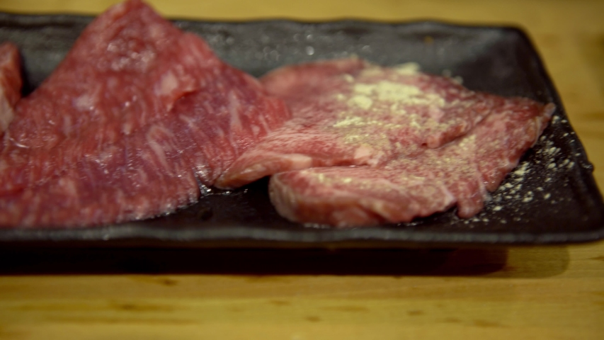 4K, Thinly sliced Japanese wagyu beef on grille for barbecue. Grill one of the best beef in Japan. Style Yakiniku meaning grilled meat cuisine. BBQ food.-Dan | Shutterstock HD Video #1053447896