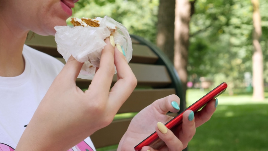Female in white T-shirt reads message on red smartphone. Woman eats piece of delicious cake. Summer park background. Break time concept | Shutterstock HD Video #1053448553