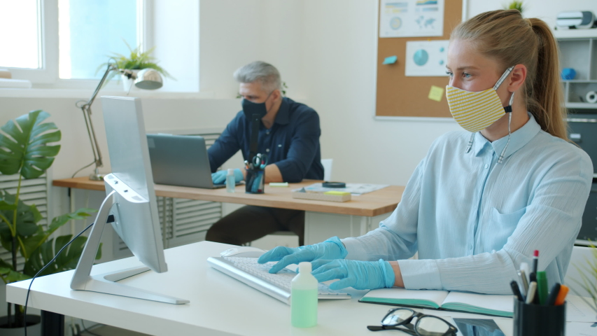 Business people in face masks and gloves are working with computers typing in office during covid 19 epidemic. Workplace, infection and technology concept. Royalty-Free Stock Footage #1053449444