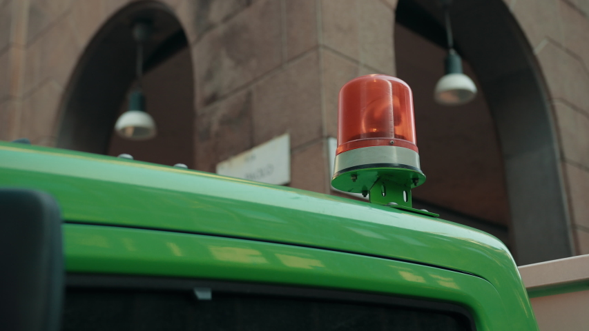 Yellow Flashing Light On Roof Of A Green Car. The Signal Revolves Around. Bright Day, Close-Up   Shutterstock HD Video #1053455024