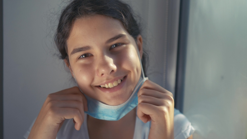 coronavirus pandemic concept. little teenage girl kid takes off medical mask and smiles a beautiful sunlight from the window. self-isolation virus covid 19 infection doomsday. coronavirus child  Royalty-Free Stock Footage #1053458912