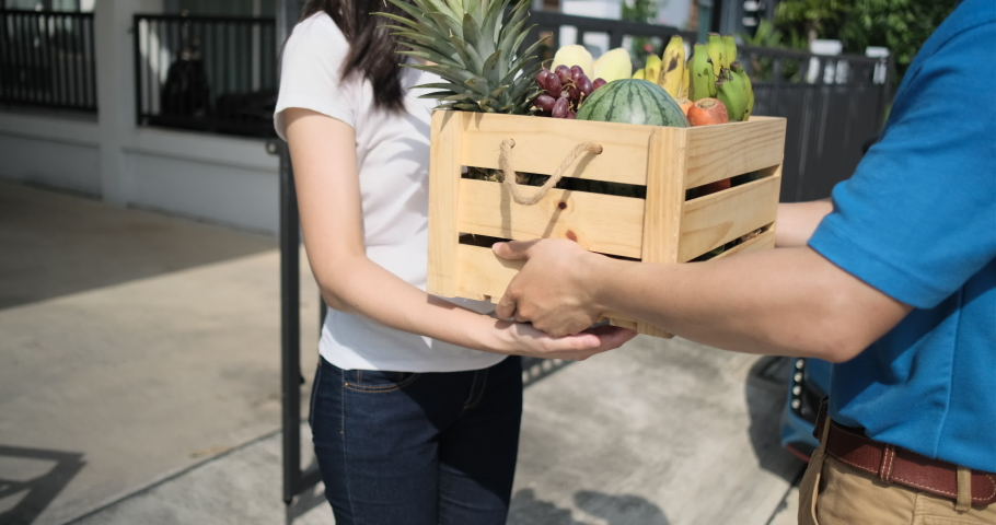 Food Deliver Asian man in blue uniform give fruit and vegetable to receiver customer front house, fast express grocery service when crisis coronavirus, covid19 new normal lifestyle concept. | Shutterstock HD Video #1053462551