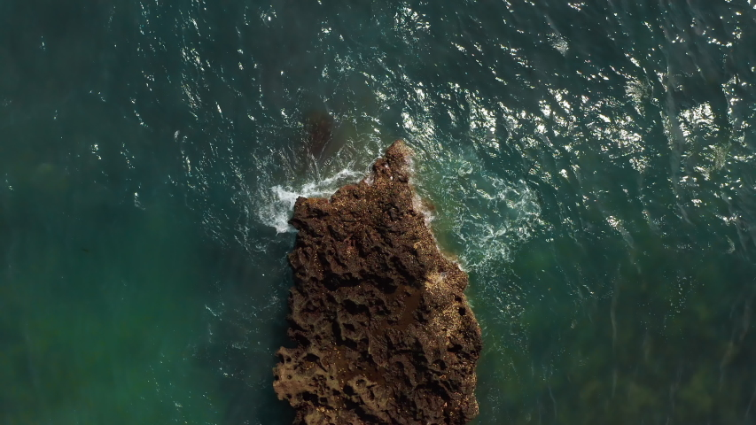 Aerial top view of waves break on rocks in a blue ocean. Sea waves on beautiful beach aerial view drone 4k shot. Bird's eye view of ocean waves crashing against an empty stone rock cliff from above. | Shutterstock HD Video #1053462596