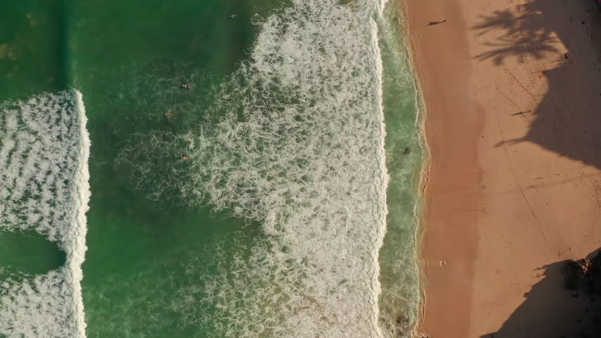 Aerial top view of ocean blue waves break on a beach. Sea waves and beautiful sand beach aerial view drone shot. Bird's eye view of ocean waves crashing against an empty sand beach from above. | Shutterstock HD Video #1053462599