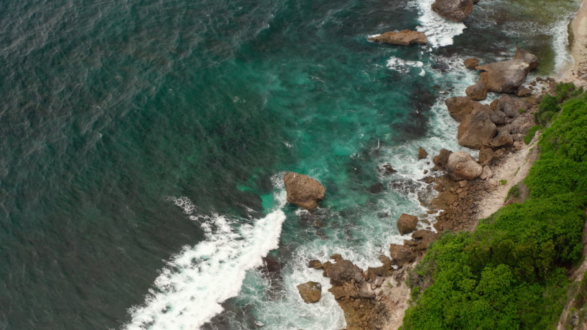 Top down aerial view from above of giant ocean waves crashing and foaming on empty sand tropical beach with big rock stones. Bird's eye aerial shot of golden beach meeting deep blue ocean water. | Shutterstock HD Video #1053462602